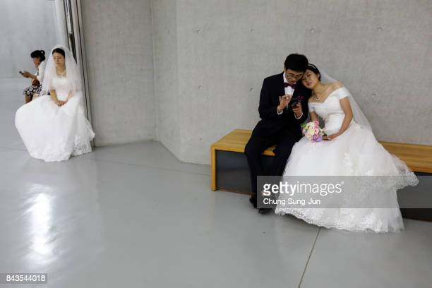 Couple wait for their wedding ceremony of the Family Federation for World Peace and Unification commonly known as the Unification Church at...