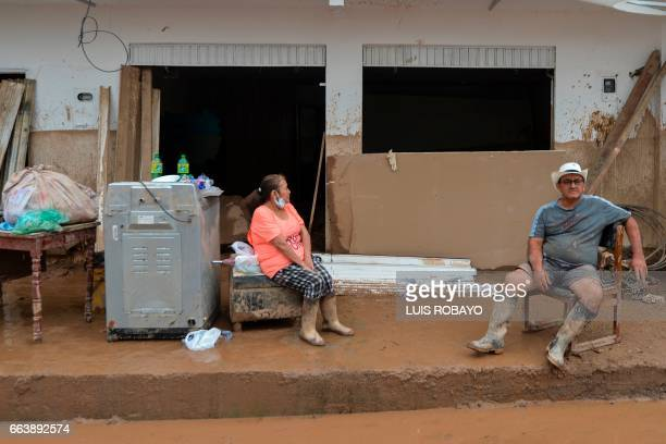 TOPSHOT A couple wait outside their home damaged by mudslides following heavy rains in Mocoa Putumayo department southern Colombia on April 2 2017...