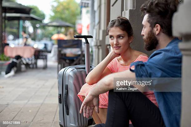 couple waiting at the doorstep with suitcase