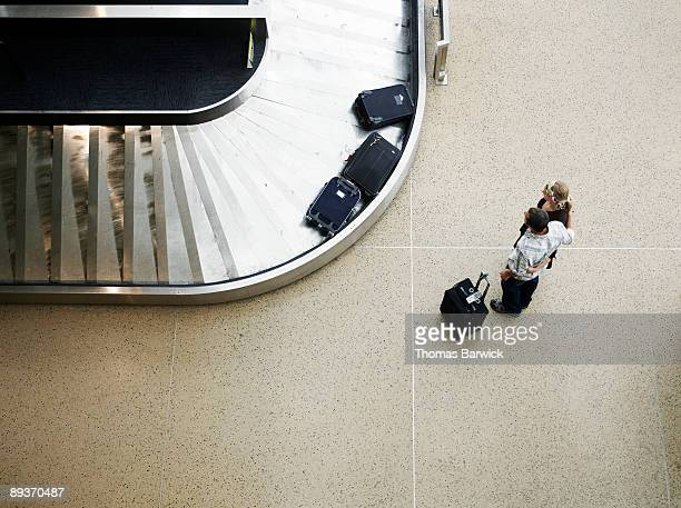 Couple waiting for luggage at baggage claim