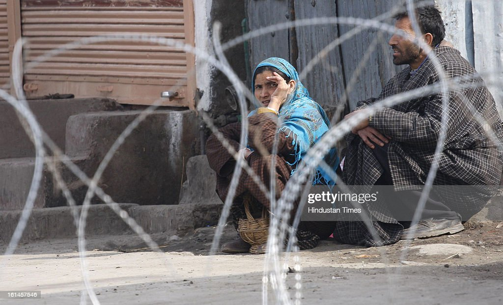 A couple waiting for the police to cross the road blocked by barbed wire on the 3rd day of curfew on February 11, 2013 in Srinagar, India. Kashmir Valley remained under curfew for the third day today even as mobile and Internet services remained suspended following hanging of Parliament attack convict Mohammad Afzal Guru.