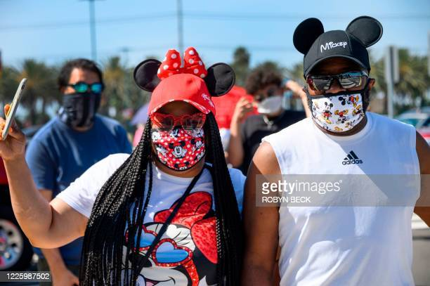 Couple waits in line to enter Downtown Disney in Anaheim, California on July 9 the first day the outdoor shopping and dining complex has been open to...