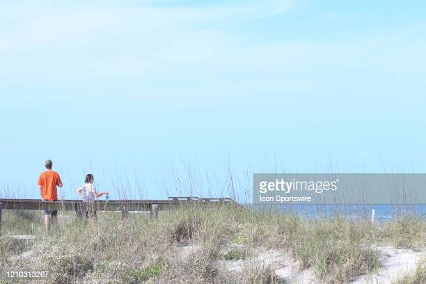 A couple waits on a public beach access prior to the beaches opening on April 17 2020 in Jacksonville Beach Fl Jacksonville Mayor Lenny Curry opened...