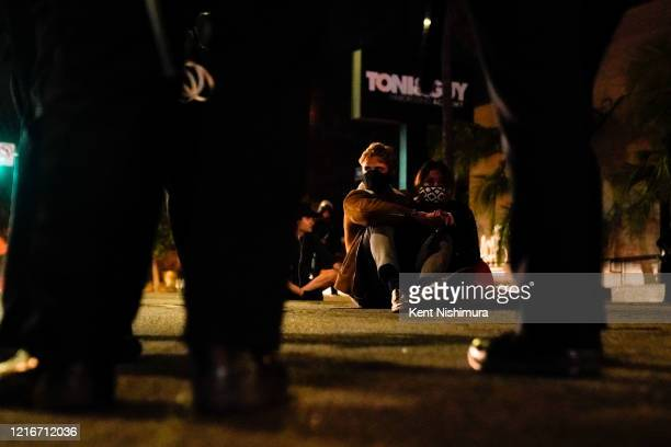 A couple waits to be processed while being arrested along with other protestors in the Fairfax District on Saturday May 30 2020 in Los Angeles CA...