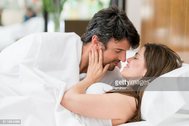 Couple waking up and woman holding his face kissing him while both are still in bed
