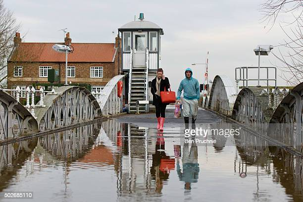 A couple walk across Cawood Bridge which crosses the River Ouse on December 28 2015 in Cawood England Heavy rain over the Christmas period has caused...