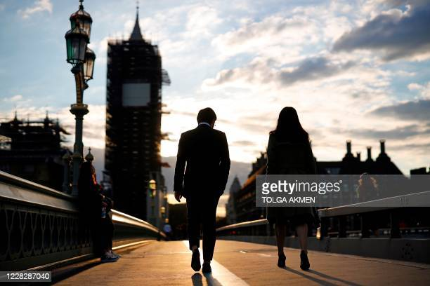 Couple walk across Westminster Bridge as the sun sets beside the Palace of Westminster, home to the Houses of Parliament in London on August 31 on...