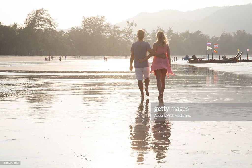 Couple walk along beach at sunrise, arm in arm : Stock Photo