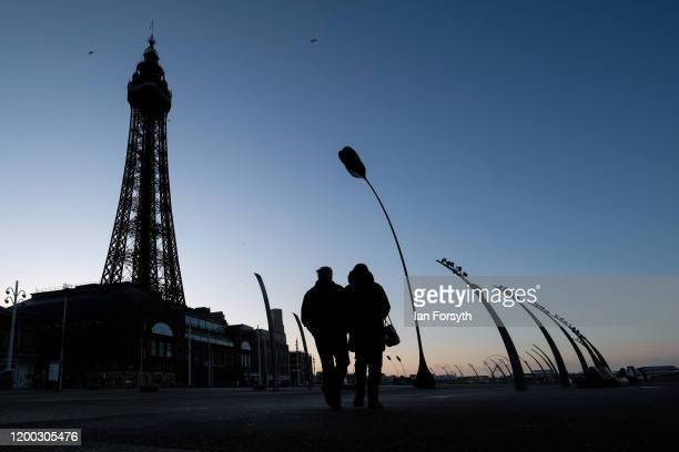 A couple walk along Blackpool seafront at first light on January 18 2020 in Blackpool England Warmer weather has taken over following the recent...