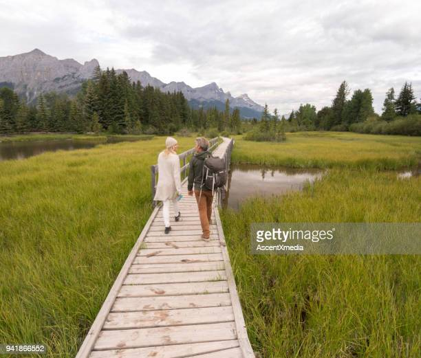 couple walk along boardwalk over marsh. - salt_marsh stock pictures, royalty-free photos & images