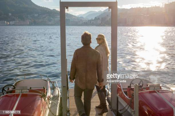 couple walk along dock on a sunny lake in the mountains - idyllic stock pictures, royalty-free photos & images