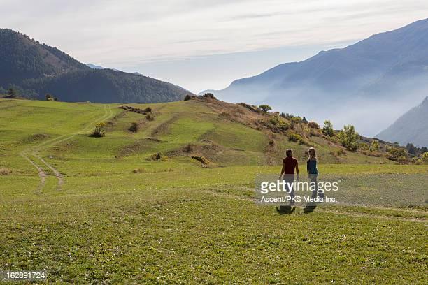 Couple walk along grass track
