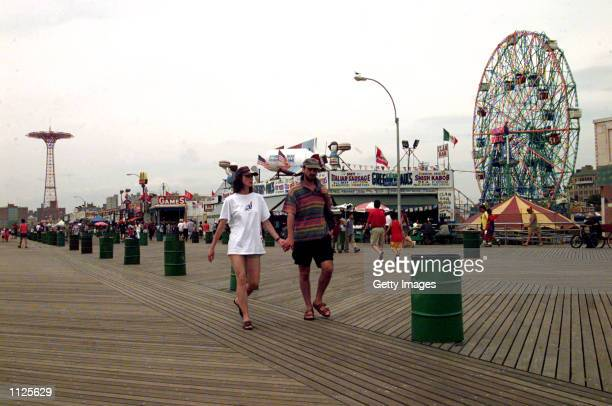 A Couple walk along the board walk opened in 1923 July 14 2002 in Coney Island New York Coney Island discovered by Dutch explorer Henry Hudson in...