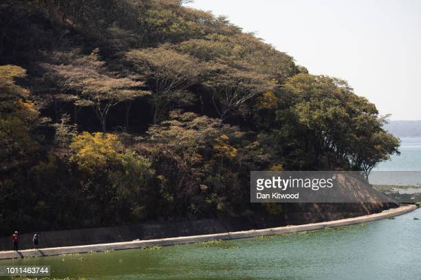 A couple walk along the dam wall at Lake Chivero on August 5 2018 in Harare Zimbabwe Lake Chivero is 32km South West of Zimbabwe's capital Harare and...