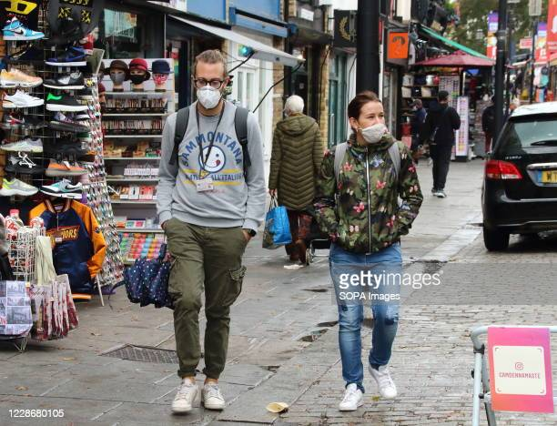 Couple walk along the streets of Camden while wearing face masks as a preventive measure against the spread of Coronavirus . Members of the public...