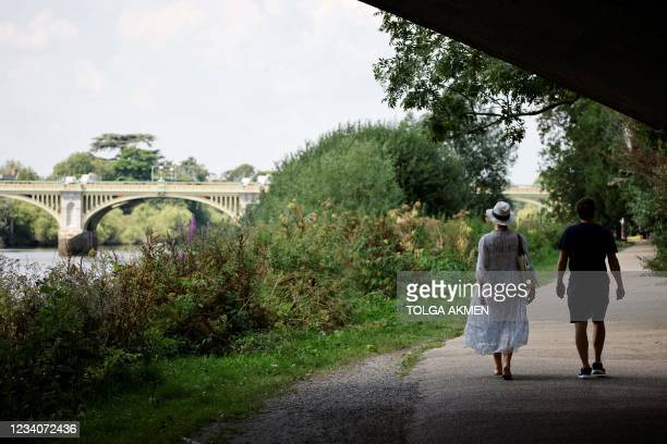 Couple walk along the towpath by the river Thames near Richmond, southwest London as temperatures soar on July 20, 2021. - Temperatures in Britain...
