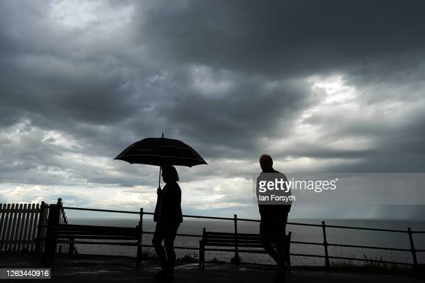 A couple walk along the upper promenade in Saltburn as thunder clouds pass overhead on August 02 2020 in Saltburn By The Sea England Heavy showers...