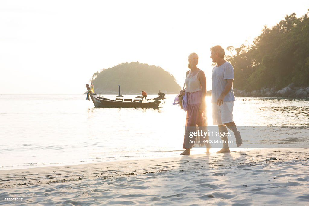 Couple walk along white sand beach, boat behind : Stock Photo