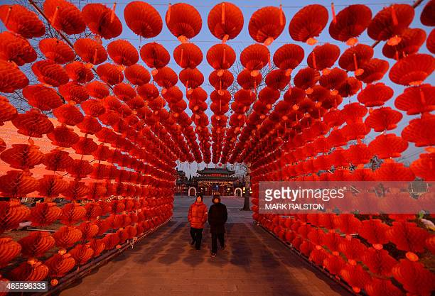 A couple walk beneath a display of lanterns for the Lunar New Year as China prepares for the Year of the Horse in Beijing on January 28 2014 China is...