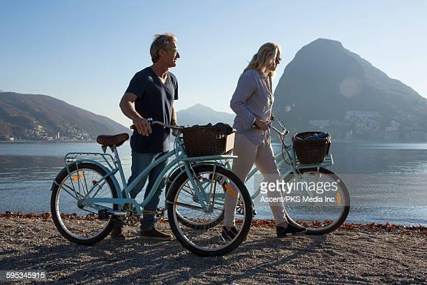Couple walk bikes by lake edge, mountains behind