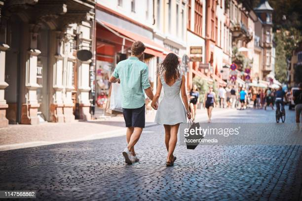 couple walk down promenade with shopping bags - blue shorts stock pictures, royalty-free photos & images