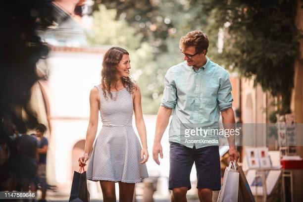 ehepaar spaziert mit einkaufstaschen die promenade hinunter - minikleid stock-fotos und bilder