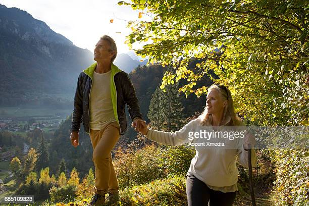 Couple walk hand in hand above forest, mtns