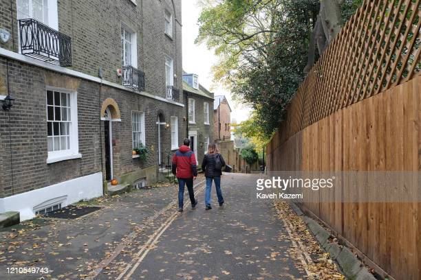 A couple walk in a narrow alley way in Hampstead village on November 3 2019 in London United Kingdom