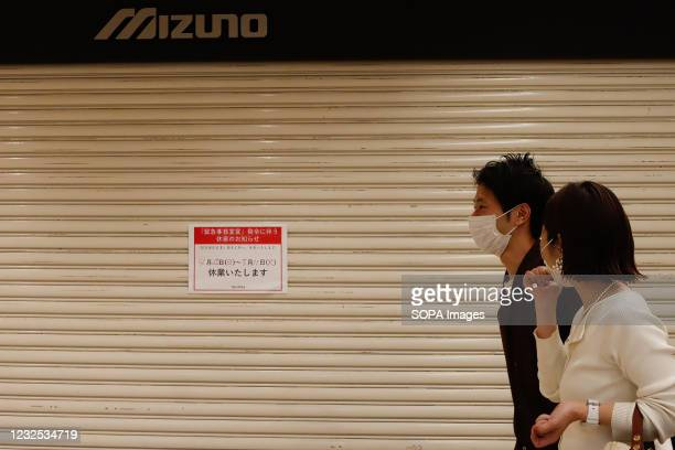Couple walk in front of a large shopping center with shutters closed during a temporary holiday in Ginza. On the 25th of the first day when the third...