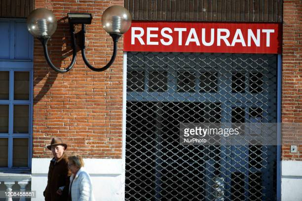 A couple walk near a closed restaurant due to the covid19 lockdown in Toulouse France on March 27 2020 The lockdown due to the Covid19 massive...