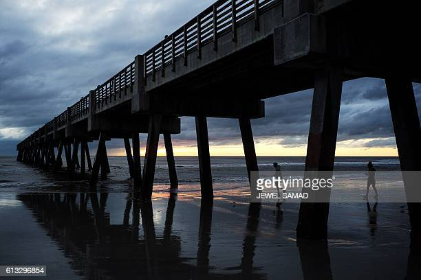 A couple walk near a pier part of which washed out in the sea in Jacksonville Beach Florida on October 8 after Hurricane Matthew passed the area A...