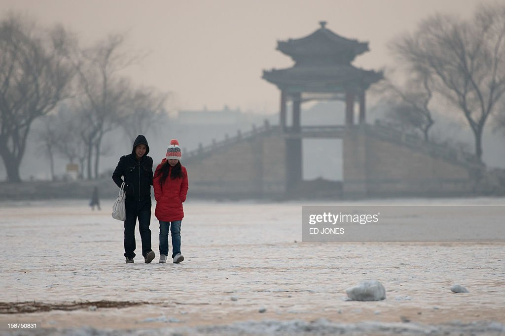 A couple walk on a frozen lake at the Summer Palace in Beijing on December 27, 2012. Forecasts were predicting temperatures of around minus 20 degrees in the run-up to January 1. AFP PHOTO / Ed Jones