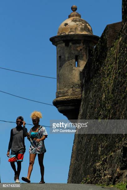 A couple walk on the road between El Morro and the fort San Cristobal in the neighbourhood of La Perla where the video Despacito was recorded in San...