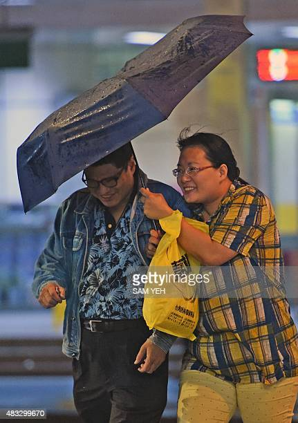 Couple walk on the street as Typhoon Soudelor approaches eastern Taiwan, in New Taipei City on August 7, 2015. An eight-year-old girl died after...