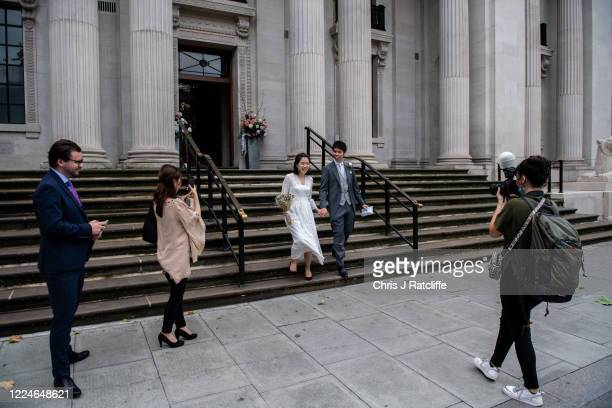 Gary Cheng and Sakiko Honda walk outside and celebrate with their wedding party of two guests and a photographer after getting married at Marylebone...