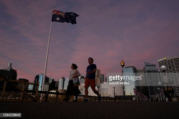 Couple walk over the bridge on the Darling Harbour at sunset in Sydney on July 27 as around half of Australia's 25 million largely unvaccinated...