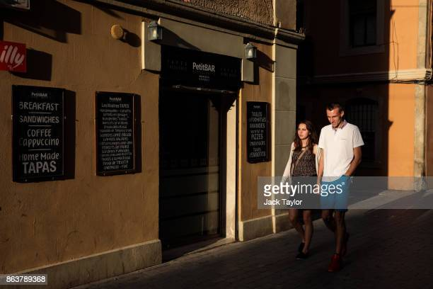 A couple walk past a a small bar as the sun begins to go down on October 20 2017 in Barcelona Spain The Spanish government is to take steps to...