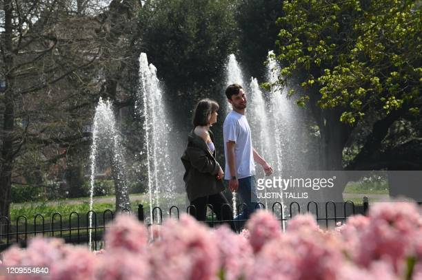 Couple walk past a colourful flower bed in the spring sunshine in Jephson Gardens in Leamington Spa in central England on April 9 as Britain...