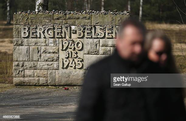 A couple walk past a memorial covered with stones left by visitors at the site of the former BergenBelsen concentration camp on March 17 2015 in...