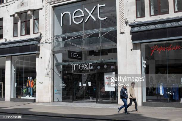 Couple walk past a Next store on Oxford Street as shops and businesses remain closed on May 01, 2020 in London, England. British Prime Minister Boris...