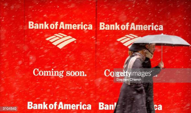 A couple walk past a window sign advertising that a Bank of America branch will be opening in the location soon March 17 2004 in New York City...