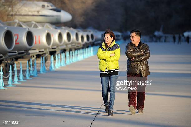 A couple walk past Chinese aircraft on display during a visit to a museum in Beijing on November 29 2013 China sent fighter jets and an early warning...