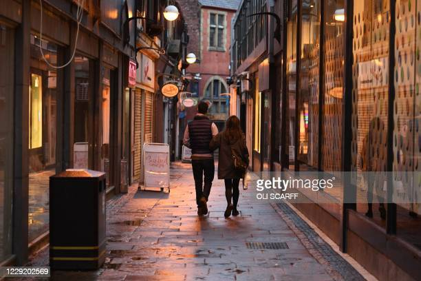 Couple walk past closed shops in a quiet lane in central Sheffield, in northern England on October 21 prior to further lockdown measures to combat...