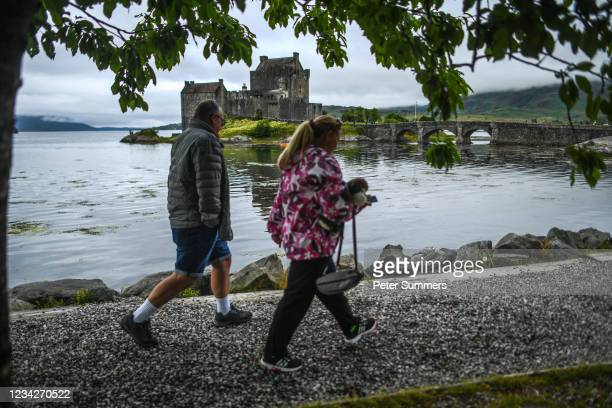 Couple walk past Eilean Donan castle on July 28, 2021 in Dornie, Scotland. Skye and Raasay attracted 650,000 visitors in pre-covid 2019 with a...