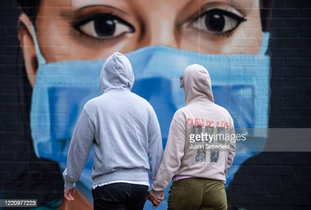 Couple walk past graffiti by artist Graffiti Life in East London on April 25, 2020 in London, England. The British government has extended the...