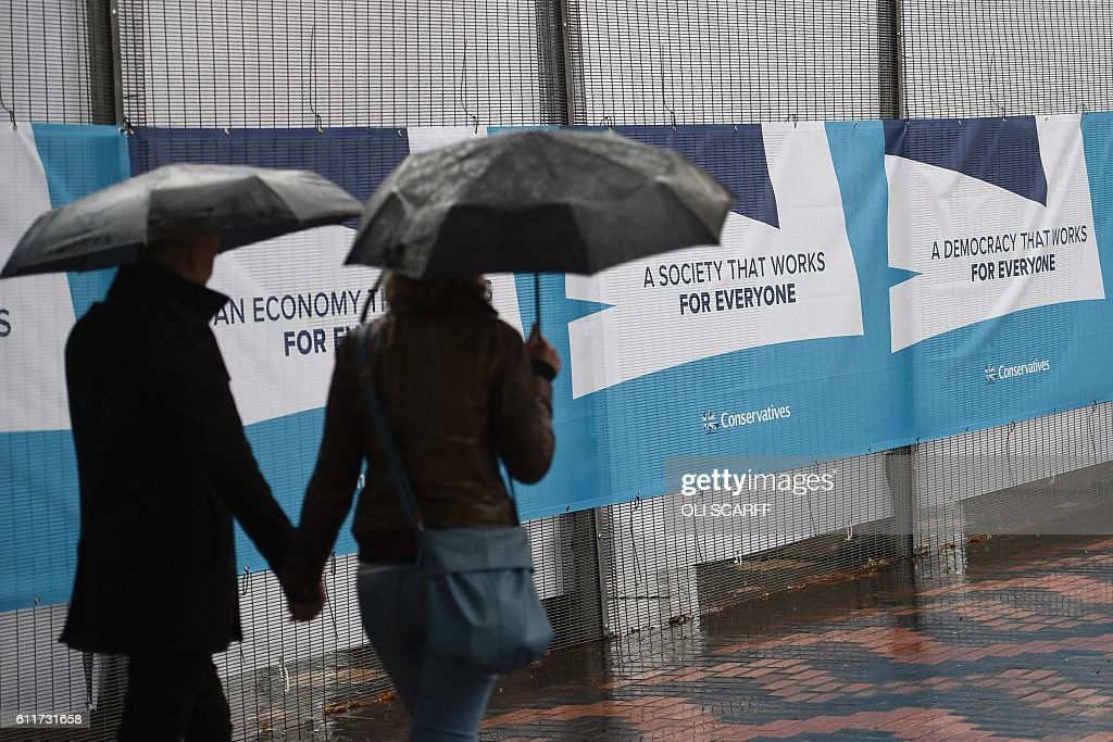 A couple walk past hording displaying Conservative Party slogans at the permimetre of the International Convention Centre in Birmingham, central England, on October 1, 2016 on the eve of the start of the ruling Conservative party annual conference. Britain's ruling Conservative party will hold its annual conference in Birmingham from October 2. / AFP / OLI