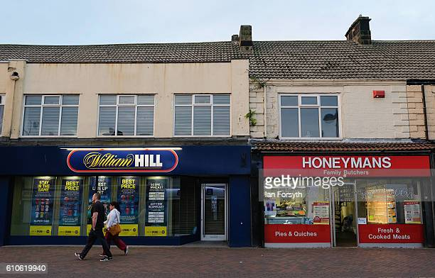 A couple walk past shop fronts in Redcar high street on September 27 2016 in Redcar United Kingdom One year on since the SSI steel making plant at...