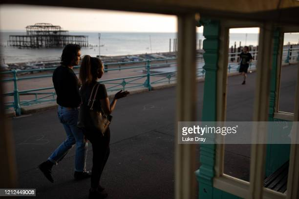 Couple walk past the Brighton West Pier on May 9, 2020 in Brighton, England. The pier closed in 1975 and subsequently fell into disrepair. On Sunday...