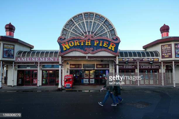 A couple walk past the entrance to North Pier on Blackpool seafront on January 18 2020 in Blackpool England Warmer weather has taken over following...