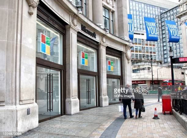 Couple walk past the Microsoft store. Microsoft has said it will keep all of its retail locations closed permanently, including London's Flagship...
